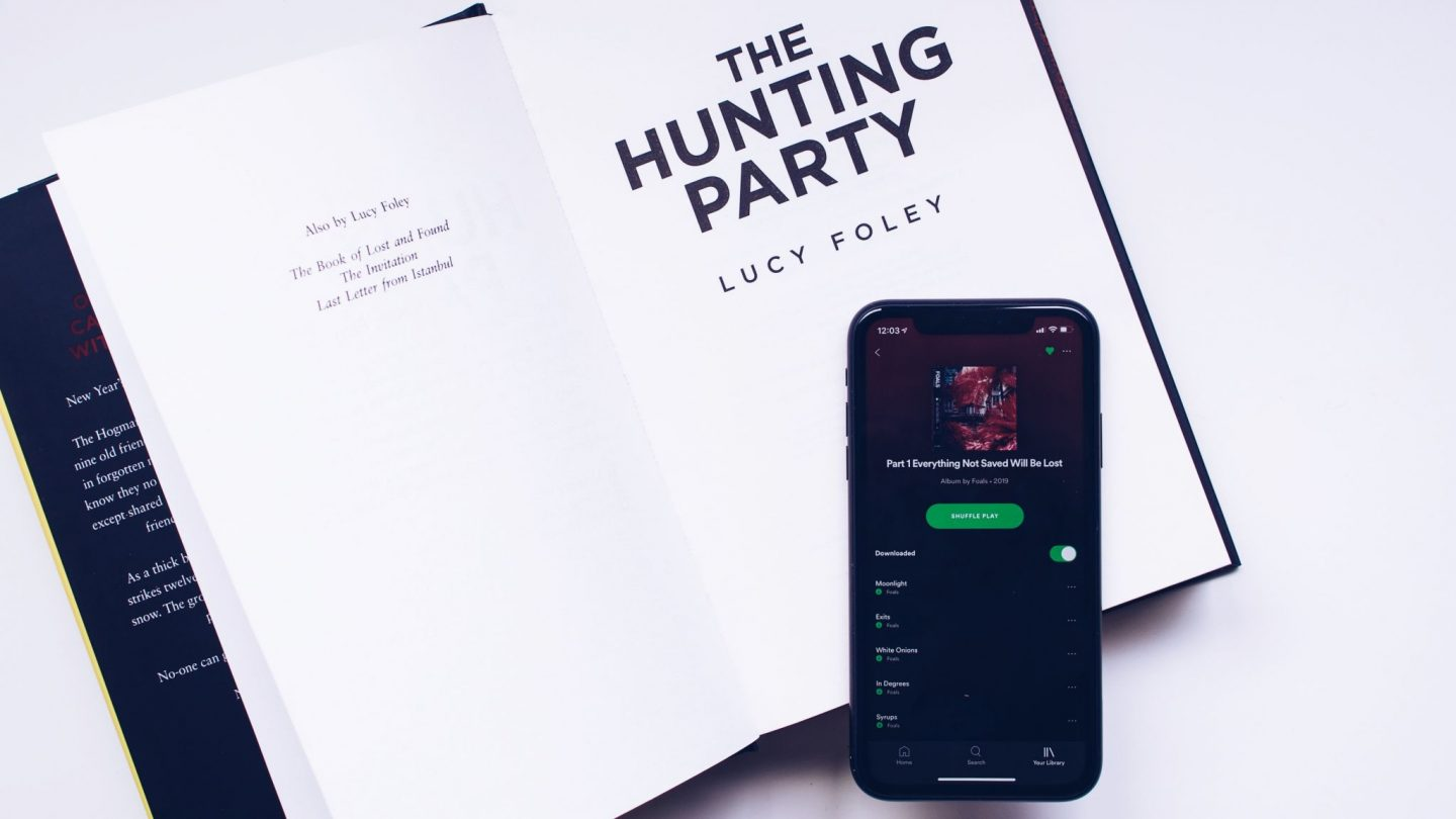March To Be Read, Listened and Watched - An open copy of The Hunting Party by Lucy Foley, with a phone on top showing the newest album by Foals